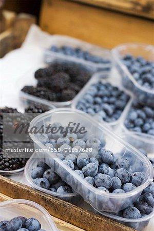 Blueberries & blackberries in plastic punnets at a market
