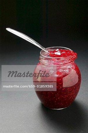 Raspberry jam in jar with spoon