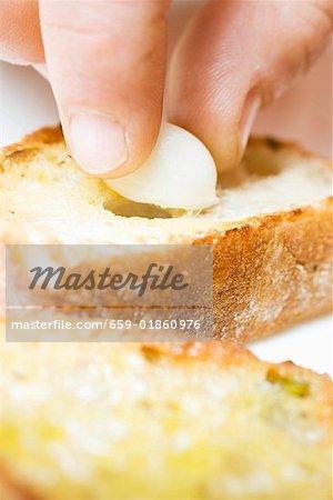 Filling baguette slice with clove of garlic