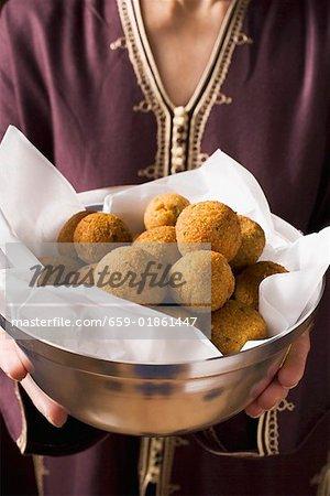 Woman serving bowl of falafel (chick-pea balls)