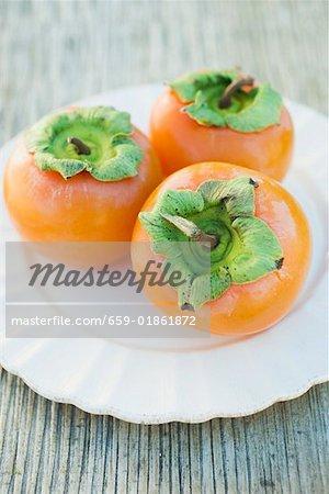 Three Sharon fruits on white plate