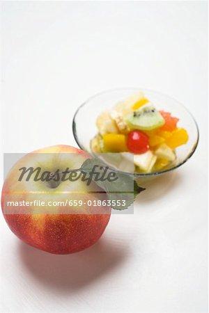 Fresh apple, fruit salad in background