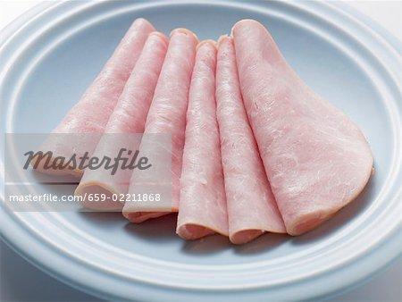Several slices of ham on light blue plate