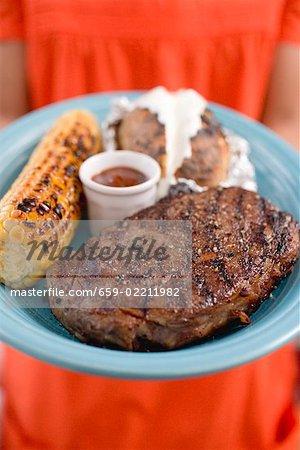 Woman holding plate of steak, corn on the cob, baked potato