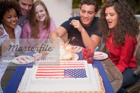 Man lighting sparklers on cake (4th of July, USA)