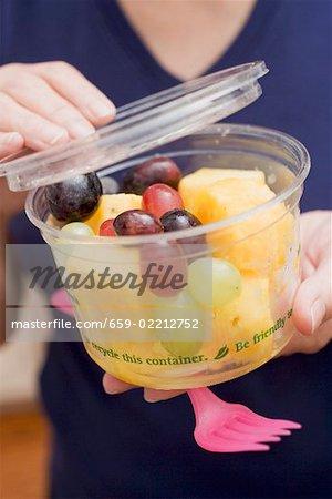 Woman holding plastic tub of fruit salad
