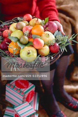 Woman holding bowl of fruit (Christmas)
