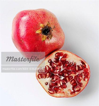 Whole pomegranate and half a pomegranate