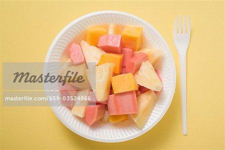 Exotic fruit salad in plastic dish (overhead view)
