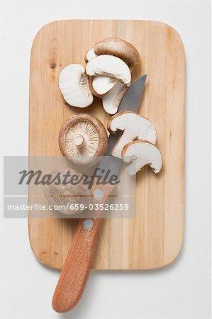 Shiitake mushrooms with knife on chopping board