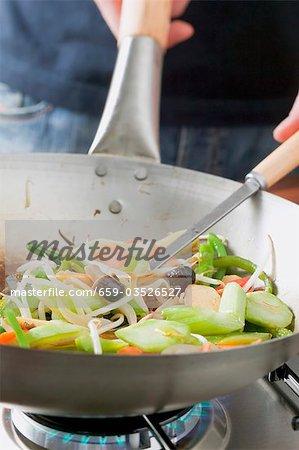 Frying Asian vegetables in frying pan