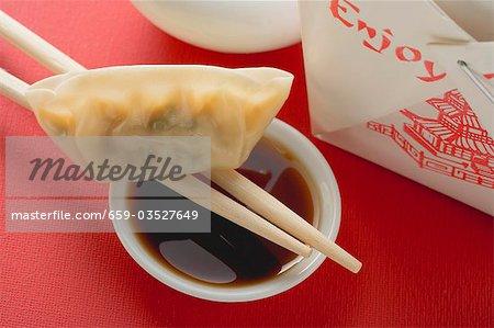 Dim sum with chopsticks and dip to take away (Asia)