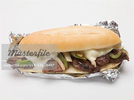 Beef, cheese, green pepper & onion sandwich in aluminium foil