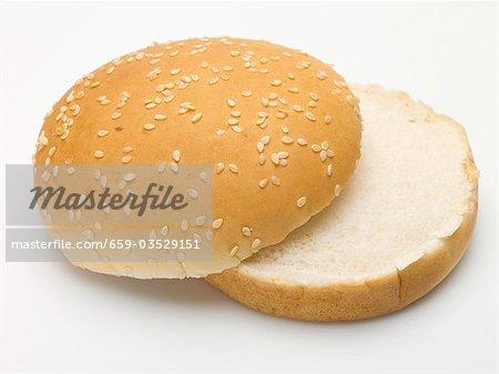 A hamburger bun with sesame seeds, split