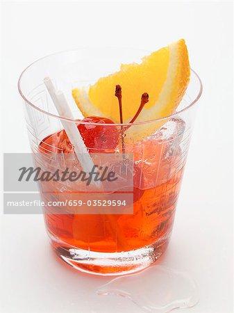 Manhattan with cocktail cherries and orange wedge