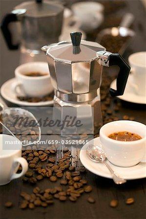 Espresso maker, cups of espresso and coffee beans