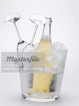 Bottle of sparkling wine & two empty wine glasses in ice bucket