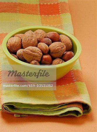 Unshelled walnuts, hazelnuts & almonds in green bowl on tea towel