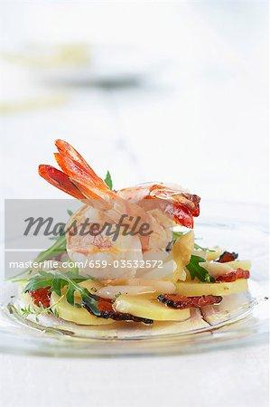 Fried prawns on potato, asparagus and ham salad
