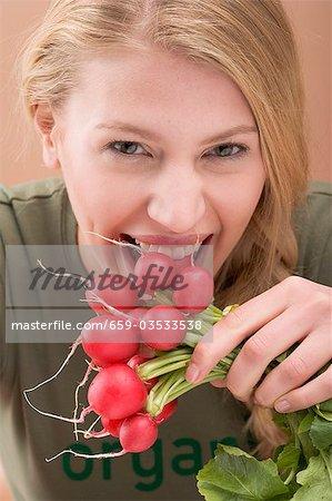 Woman biting a radish