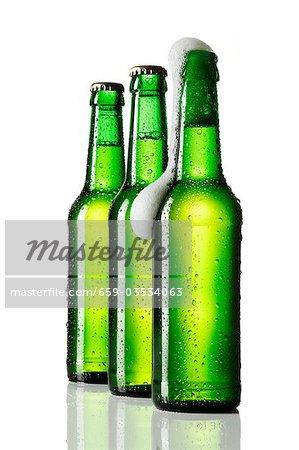 Three bottles of beer, one opened