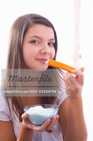 Girl eating a carrot with yoghurt dip