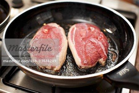 Frying duck breast, skin-side down