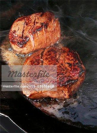 Fillet steaks sizzling in frying pan