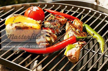 Pork kebabs and vegetables on barbecue rack