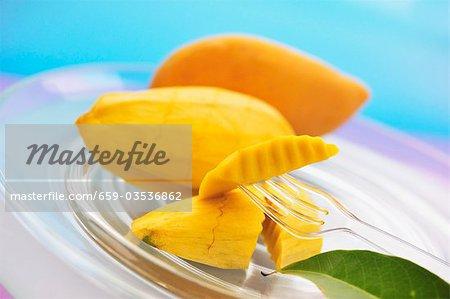 Yellow Thai mangos, peeled and unpeeled