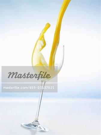 Pouring orange juice into a glass (splash)