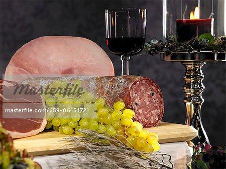Salami, ham and grapes on a chopping board