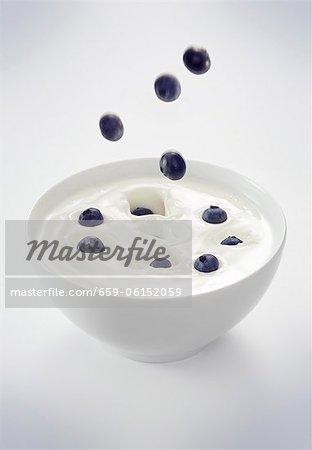 Blueberries falling into a bowl of yogurt