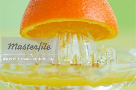 An orange half on a juicer