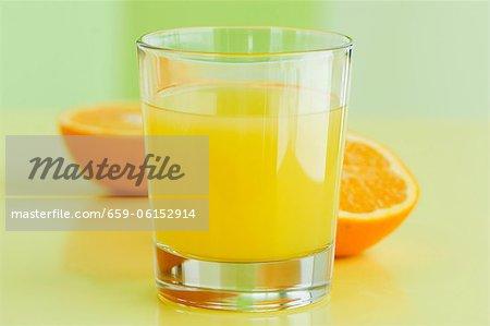 A glass of orange juice with orange halves behind it