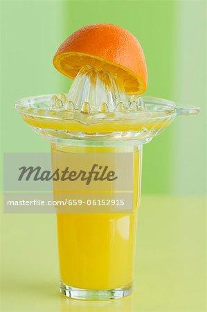 A glass of orange juice, a juicer and an orange half