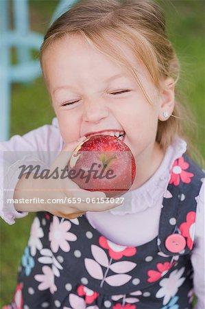 A girl biting into an apple