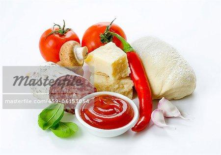 Pizza ingredients: tomatoes, a ball of dough, parmesan, Italian salami, garlic, ketchup, mushrooms