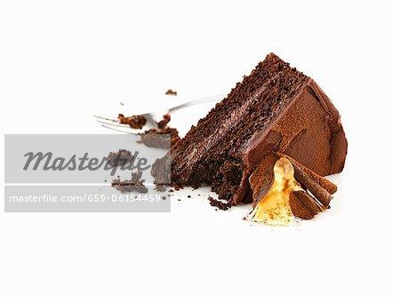 A piece of chocolate cake, partially eaten