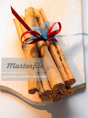 A bundle of cinnamon sticks on chopping board