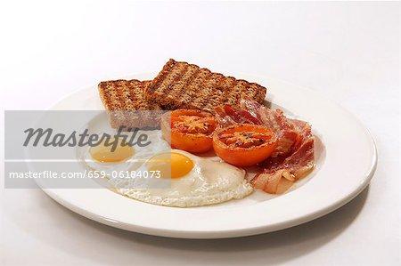 English breakfast (fried egg, bacon, wholemeal toast, tomatoes)