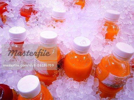 Bottles of freshly pressed fruit juice on ice