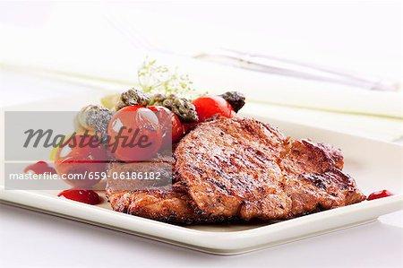 Grilled pork collar steak with a side of vegetables