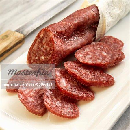 Salchichon De Vic; Catalonian Style Dry Salami; Sliced on Cutting Board