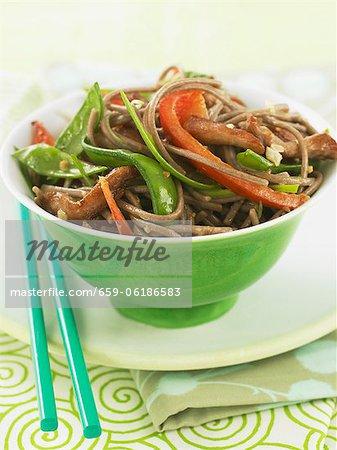Pork and Veggie Stir Fry Over Soba Noodles in a Green Bowl with Chopsticks