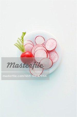 A whole radish and sliced radishes