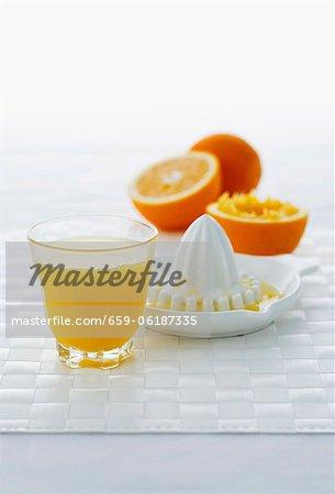 A glass of orange juice, citrus squeezer and oranges