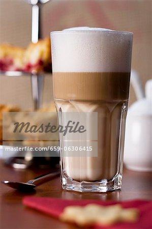 A latte macchiato in front of a cake stand