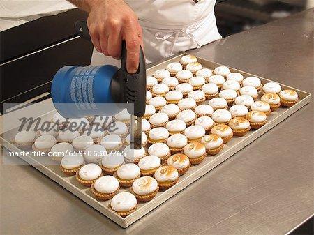 Lemon cupcakes being caramelised with a gas burner
