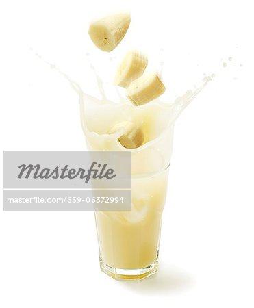 Banana slices falling into a glass of banana juice